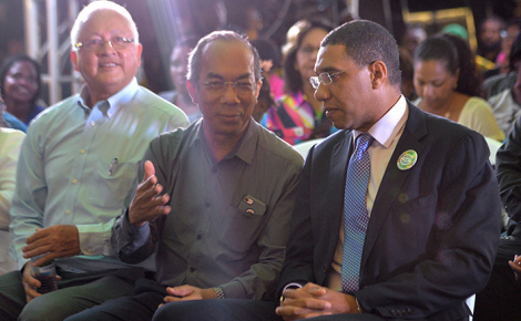 Prime Minister, the Most Hon. Andrew Holness (right), listens to Minister without Portfolio in the Ministry of Economic Growth and Job Creation, Hon. Dr. Horace Chang (centre), at a town hall meeting in Barbican Square, St. Andrew, on September 21. At left is Minister of Justice, Hon. Delroy Chuck, who is also Member of Parliament for North East St. Andrew.