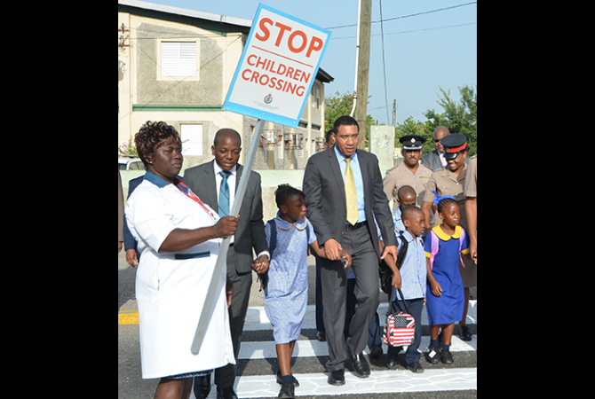Prime Minister, the Most Hon. Andrew Holness (4th left), helps children to cross the street outside of the Seaward Primary and Junior High School on Olympic Way in St Andrew, as they began the first day of the academic year in September 2016. At 2nd left is State Minister for National Security, Hon. Pearnel Charles Jnr.