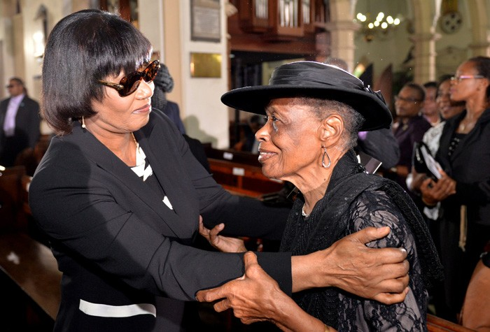 Prime Minister, the Most Hon. Portia Simpson Miller (left), consoles Mrs. Iona deSouza, widow of retired Bishop of the Diocese of Jamaica and the Cayman Islands, the Right Rev. the Hon. Dr. Neville deSouza, who was laid to rest, today (December 29), following an official funeral service at the St. Andrew Parish Church, in St. Andrew.