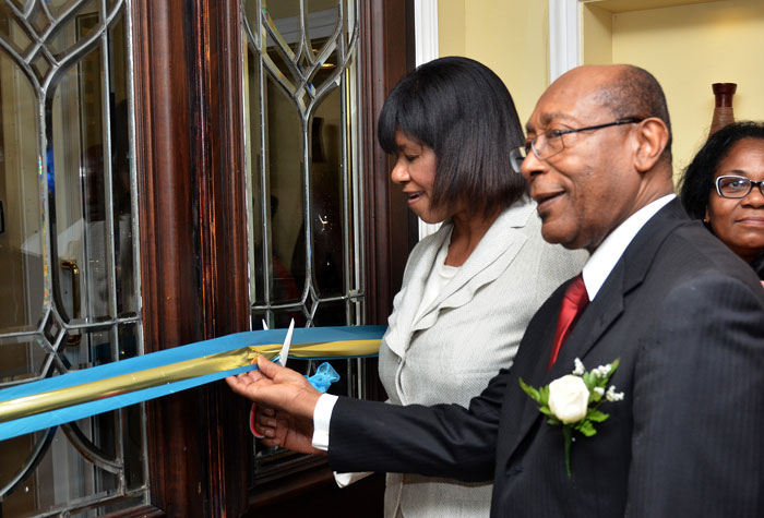 Prime Minister the Most Hon. Portia Simpson Miller (left), is assisted by  and Executive Chairman, Eden Gardens Wellness Resort and Spa, Dr. Henry Lowe, as she cuts the ribbon  to launch the newly redeveloped facility on March 25, at its Lady Musgrave Road location, in Kingston.