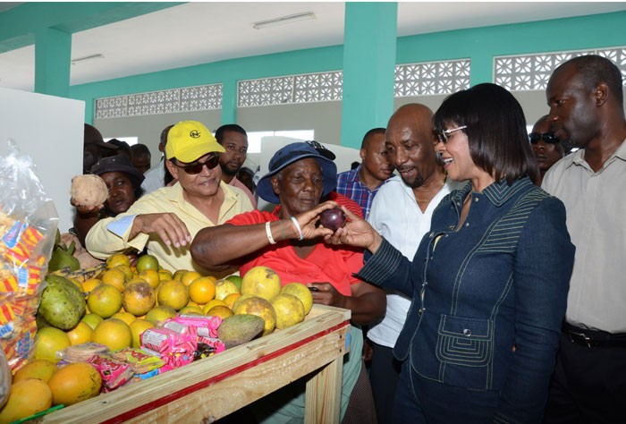 Prime Minister the Most Hon. Portia Simpson Miller (second right) admires a star apple being sold by a vendor inside the newly constructed Rocky Point Market in Clarendon on April 12, during a tour of the facility. With the Prime Minister are (from left); Minister of Local government and Community Development, Hon. Noel Arscott; Member of Parliament, South East Clarendon, Rudyard Spencer; and Mayor of May Pen, Councillor Scean Barnswell.