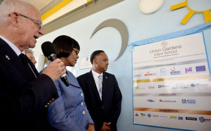 Prime Minister, the Most Hon. Portia Simpson Miller (centre), looks at a plaque detailing the sponsors of the state-of-the-art Union Gardens Infant School, at the official opening of the institution on Wednesday, January 13. Others (from left) are: Minister of Education, Hon. Rev. Ronald Thwaites; and Managing Director of the Jamaica Social Investment Fund (JSIF), Mr. Omar Sweeney. The school, located in South West St. Andrew was constructed last year through the collaboration of several public and private partners.