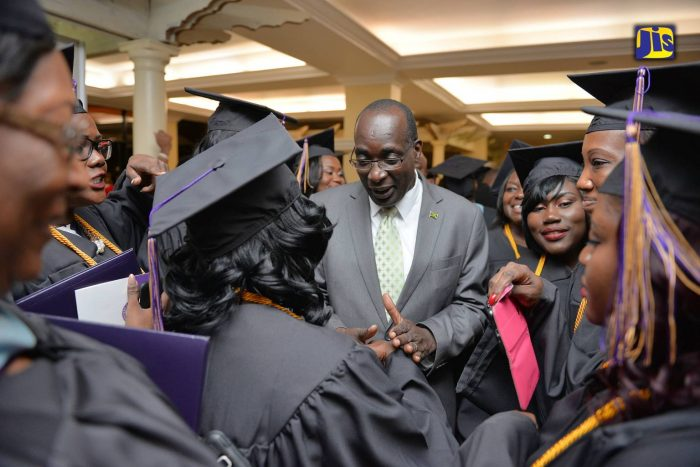 Education, Youth and Information Minister, Senator the Hon. Ruel Reid (centre), conversing with graduates of Western Carolina University following the institution's fall commencement, which was held at the Knutsford Court Hotel in New Kingston on Friday, October 21.