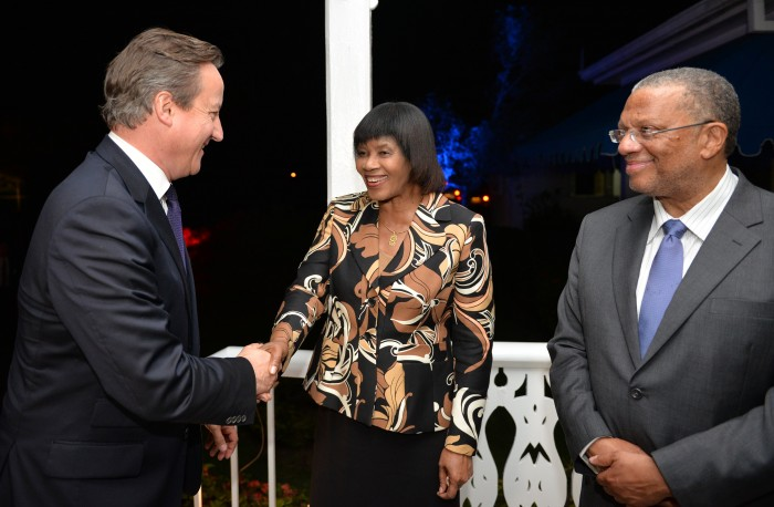 Prime Minister, the Most Hon. Portia Simpson Miller (centre), welcomes Prime Minister of the United Kingdom (UK), the Rt. Hon. David Cameron (left), while Minister of Finance and Planning, Dr. Hon. Peter Phillips shares the moment. Occasion was a reception in Mr. Cameron's honour held last evening (Sept. 29) at Vale Royal in Kingston. Prime Minister Cameron departed the island this morning (Sept. 30), after addressing a joint sitting of Parliament.