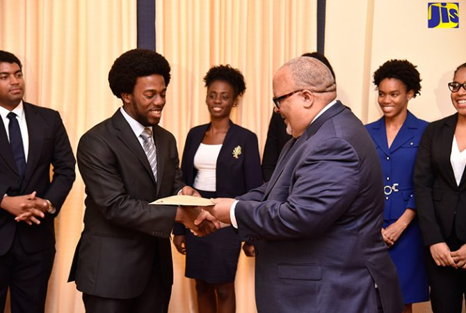 2018 Rhodes Scholar, Jelani Munroe (left), collects his Letter from former Rhodes Scholar, Peter Goldson, at King's House on November 16. In the background are the other finalists.