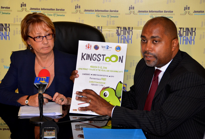 Science, Technology, Energy and Mining State Minister, Hon. Julian Robinson (right), dislays a poster promoting the KingstOOn animation conference and film festival, during a recent Jamaica Information Service (JIS) Think Tank.  Looking on is World Bank Country Manager for Jamaica, Galina Sotirova.