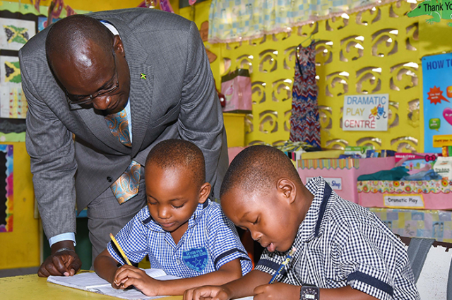 Education, Youth and Information Minister, Senator the Hon. Ruel Reid, looks on as five-year-old Devon Primary and Infant School students, Quewayne Davis (centre) and Jayquon McIntosh, demonstrate their writing skills. Occasion was a visit to the institution on Wednesday (September 20), during the Minister's tour of institutions in St. Mary.