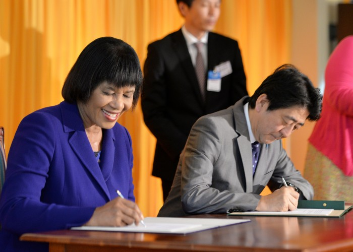 Prime Minister, the Most Hon Portia Simpson Miller (left), and Prime Minister of Japan, His Excellency, Mr. Shinzo Abe, sign an agreement at Jamaica House on Wednesday (September 30), for the provision of grant funding to the Institute of Jamaica (IOJ).