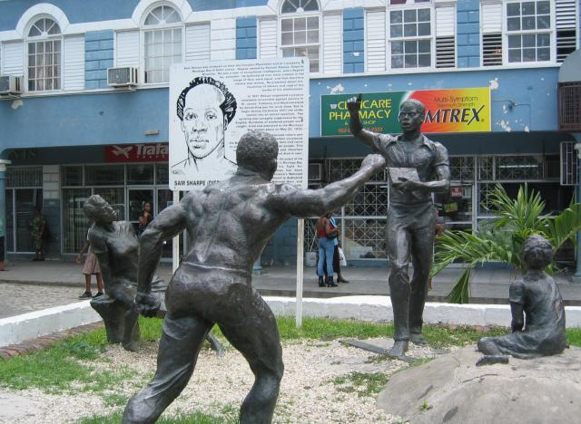 The Sam Sharpe Monument, designed by Kay Sullivan, portrays Sharpe holding his Bible and speaking to his people. The five statues were cast in bronze in Jamaica.