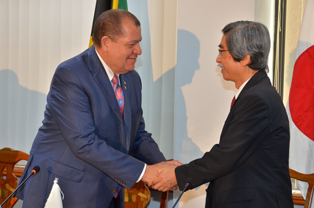 Finance and the Public Service Minister, Hon. Audley Shaw (left), greets Japan's Ambassador to Jamaica, Ambassador Masanori Nakano, during Wednesday's (April 12), signing ceremony for the implementation of a $348.9 million (¥300 million/US$2.7 million) grant-funded three-year 'Project to Promote Energy Efficiency in Caribbean Countries' at the Ministry's offices in Kingston.