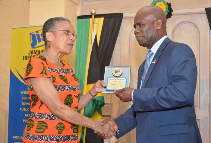 Deputy Governor General, the Hon. Steadman Fuller receives a plaque from Chairman of the Jamaica Information Service (JIS) Advisory Board, Ms. Fae Ellington, at the 2015 JIS Heritage Essay Competition Awards Ceremony, held on November 27, at King's House.