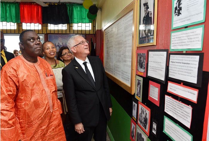 Min. Thwaites looks at photo of Marcus Garvey in the Resource Centre at school. Looking on is Amb. Olatokunboh Kamson, Nigerian High Commission to Jamaica and Mathu Joyini, South African High Commissioner to Jamaica.