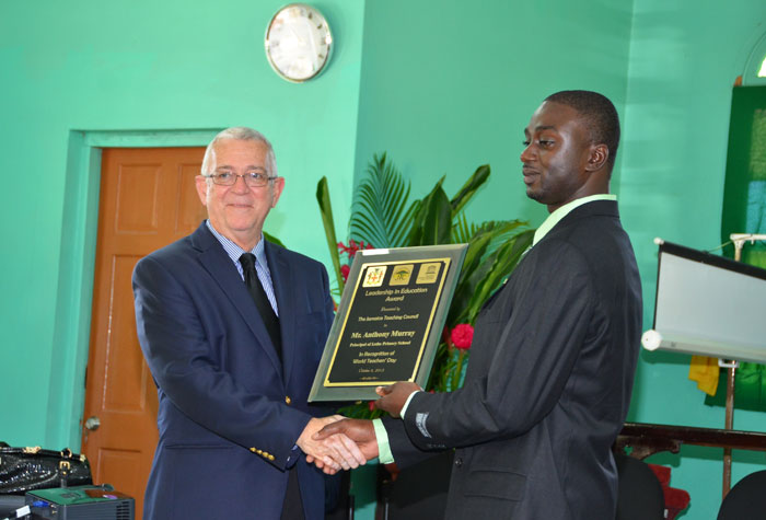 Minister of Education, Hon. Rev. Ronald Thwaites (left), presents Principal of the Lethe Primary School, Anthony Murray, with the Citation for the Leadership in Education Award, during a ceremony held at the school in Lethe, St. James, on November 29. The ceremony was held to honour the principal who has won the Award for his distinguished service in education.