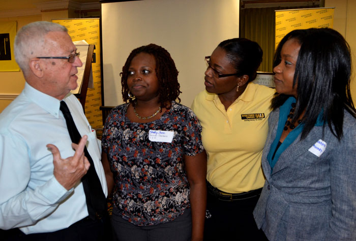 Minister of Education Hon. Rev. Thwaites (left) enjoys a conversation with (from right): Teacher at Mona Heights Primary, Dionne McKreth; Marketing Manager at Western Union Jamaica, Vinette Rowe; and teacher at Norman Gardens Primary and Junior High School, Shelly Ann Webber Hibbert. They were attending the Western Union Teachers' Workshop, held at the Knutsford Court Hotel on April 11, 2014.