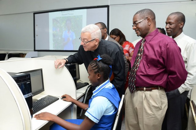 Windward Road Primary and Junior High School student, Princess Rainford (seated), demonstrates her proficiency of the computer to Minister of Education, Rev. Hon. Ronald Thwaites (2nd right). The Minister was touring sections of the school, during a visit to the institution's East Kingston location on October 24. Looking on at right, is principal, Norman Malcolm. (FILE)
