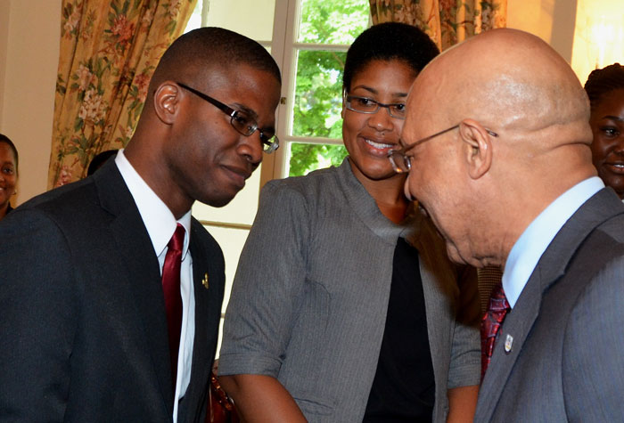 Governor-General, His Excellency the Most Hon. Sir Patrick Allen (right), congratulates Timar Jackson (left) on being named the 2014 Rhodes Scholar during a brief ceremony at King's House on November 21.