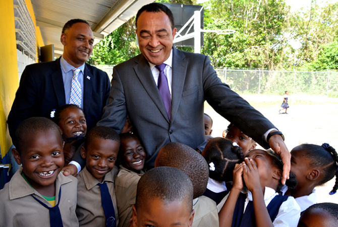 Health Minister and Member of Parliament for West Central St. Catherine, Hon. Dr. Christopher Tufton (right), interacts with students of the Brown's Hall Primary School in the parish, at Wednesday's (April 12) handing over of a $60 million expansion project, which was financed by the Jamaica Social Investment Fund (JSIF). Sharing the moment at left is Managing Director of JSIF, Omar Sweeny.