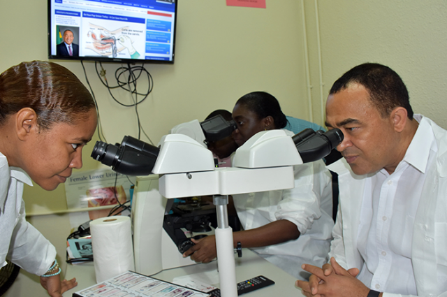 Health Minister, Dr. the Hon. Christopher Tufton (right), and Acting Coordinator for Medical Technology Services at the National Public Health Laboratory in Kingston, Michelle Maylor-Archat (left), peer through microscopes during a tour of the institution on Friday, February 10. The tour followed the presentation of a newly acquired Real Time Polymerase Chain Reaction (PCR) machine, valued approximately $6.4 million (US$50,000), to the Laboratory by the Pan American Health Organization/World Health Organization (PAHO/WHO). Also pictured is Chief Medical Technologist in the Cytology Department, Cecile Appiah.
