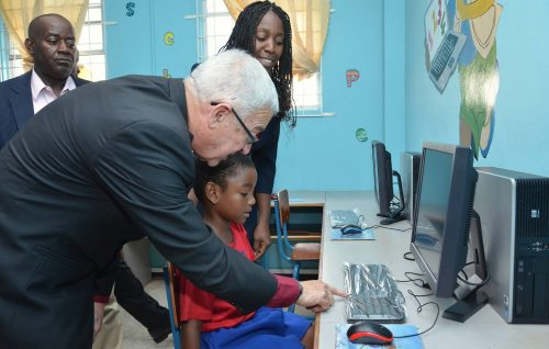 Minister of Education, Rev. Hon. Ronald Thwaites (right), explains the use of the computer keyboard to young Gerald Bolton (seated), at the opening of the refurbished laboratory at the Voluntary Organization for the Upliftment of Children (VOUCH) in Kingston on February 21. Others looking on are: President Elect, Jamaica Teachers' Association (JTA), Doran Dixon; and Principal, VOUCH, K. Bromfield. Ten computers, valued at $600,000, were donated by the JTA.