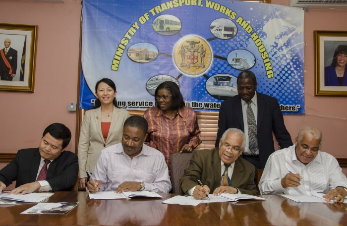 Minister of Transport, Works and Housing, Dr. the Hon. Omar Davies (3rd left), signs a Memorandum of Understanding (MOU), with China Engineering Company (CHEC) for a feasibility study on the damming of the Bog Walk Gorge, at the  Ministry in Kingston, on March 28. Also participating are (from left): Ambassador of the People's Republic of China in Jamaica, Mr. Xiaojun Dong;  Minister of Science, Technology, Energy and Mining, Hon. Phillip Paulwell;  and Minister of Water, Land, Environment and Climate Change, Hon. Robert Pickersgill. In the back row (from left) are: Commercial Counsellor at the Embassy of the People's Republic of China,  Mrs. Lei Liu (left); Permanent Secretary in the Ministry of Transport, Works and Housing, Mrs. Audrey Sewell and Permanent Secretary in the Ministry of Water, Land, Environment and Climate Change,  Dr. Alwin Hayles.