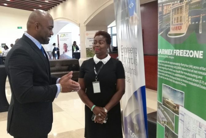 Minister of Science, Energy and Technology, Dr. the Hon. Andrew Wheatley (Left), speaks with President of the Business Process Industry Association of Jamaica (BPIAJ), Gloria Henry, on the final day of the two-day Outsource2Jamaica inaugural Symposium and Expo held at the Montego Bay Convention from April 12 to 13.